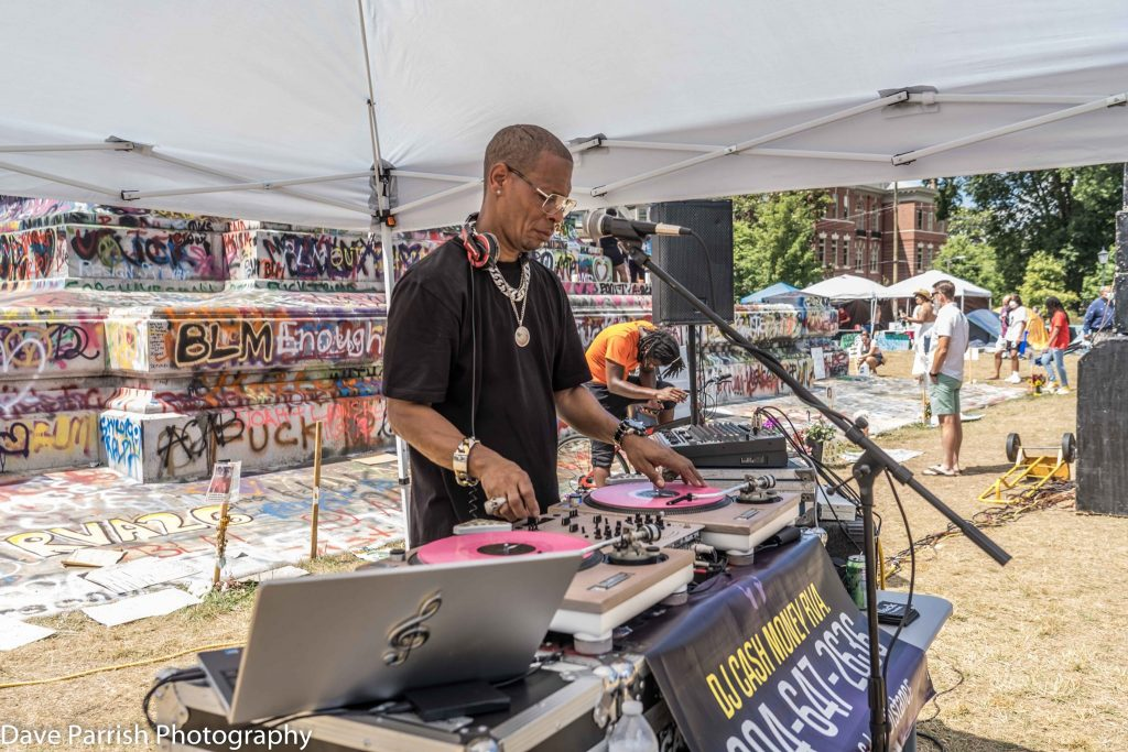 DJ Cash Money spins records at event in front of General Lee statue.