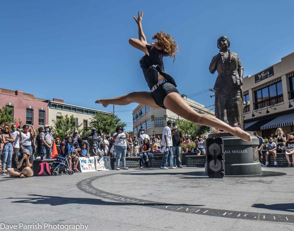 Black female dancer leaps in air during dance performance at protest in front of Maggie L. Walker statue in Richmond