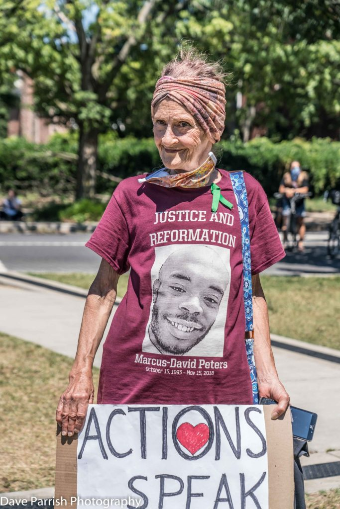 """Elderly white woman holding """"actions speak"""" sign and wearing a Marcus-David Peters shirt"""