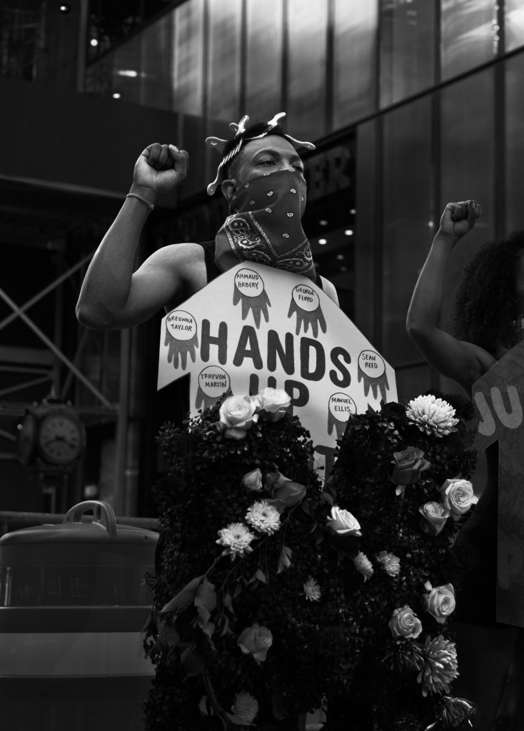 Woman holding up Black power sign and carrying flowers during protest
