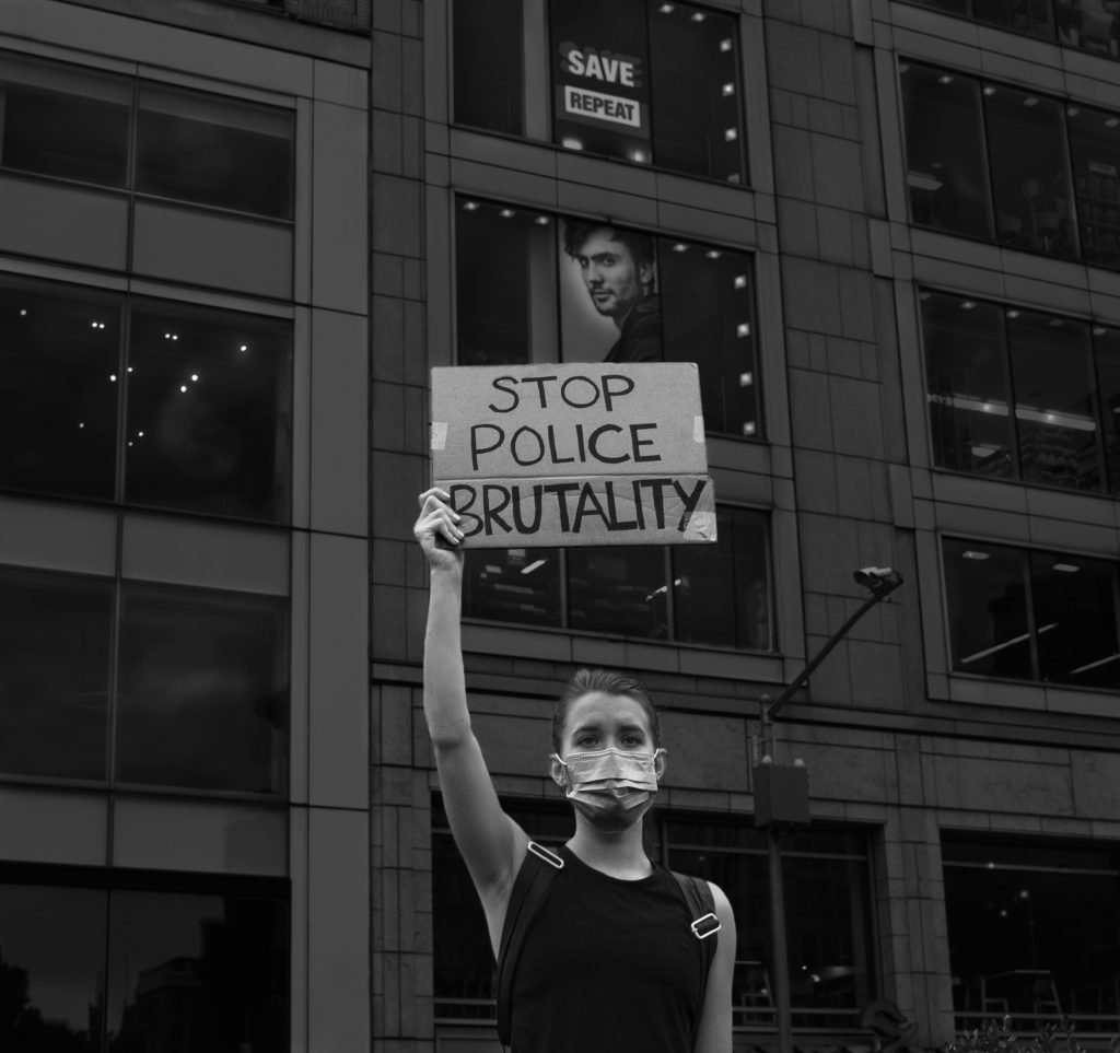 """Woman holding a """"Stop Police Brutality"""" sign"""
