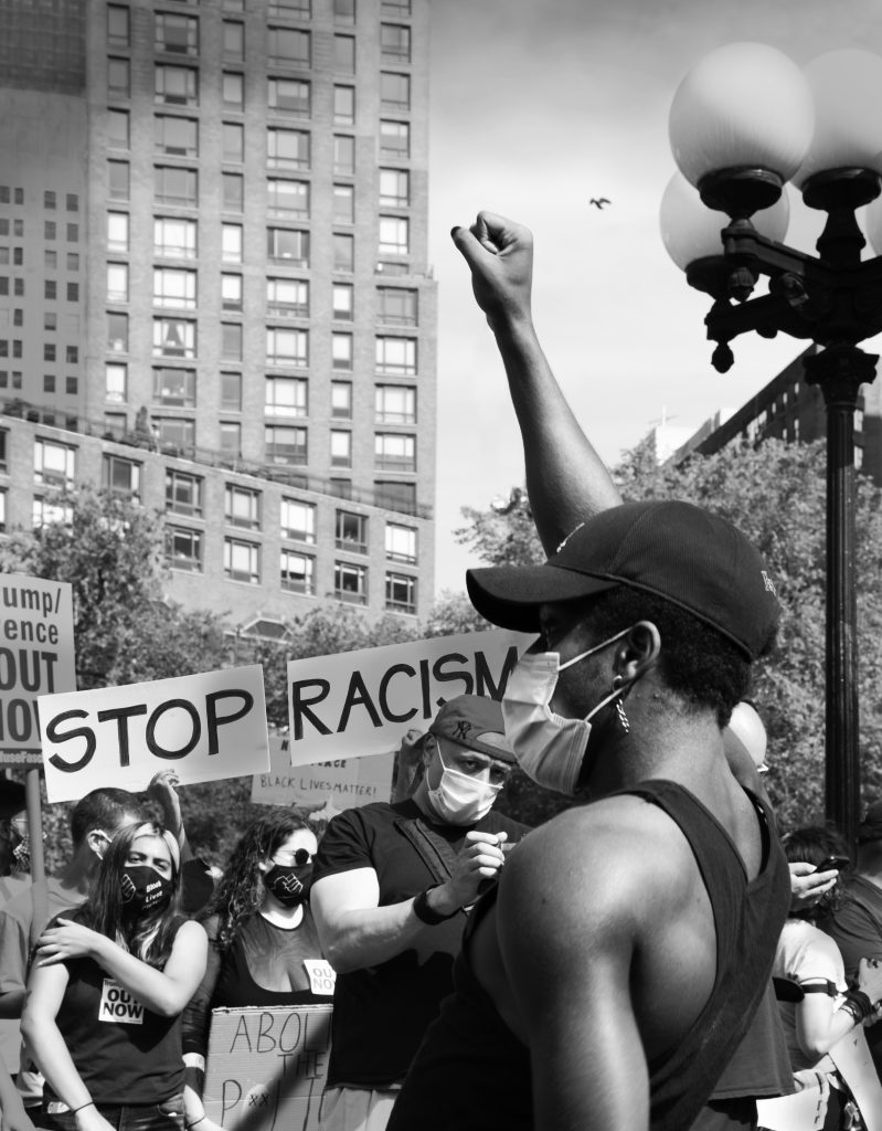 """Woman holding up black power fist at protest in front of """"Stop Racism"""" signage"""