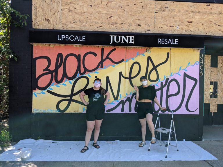 artists pose in front of Black Lives Matter mural