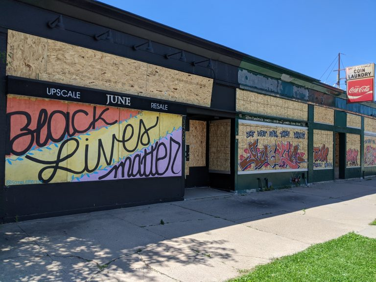 Wide view of murals on boarded storefronts in Minneapolis
