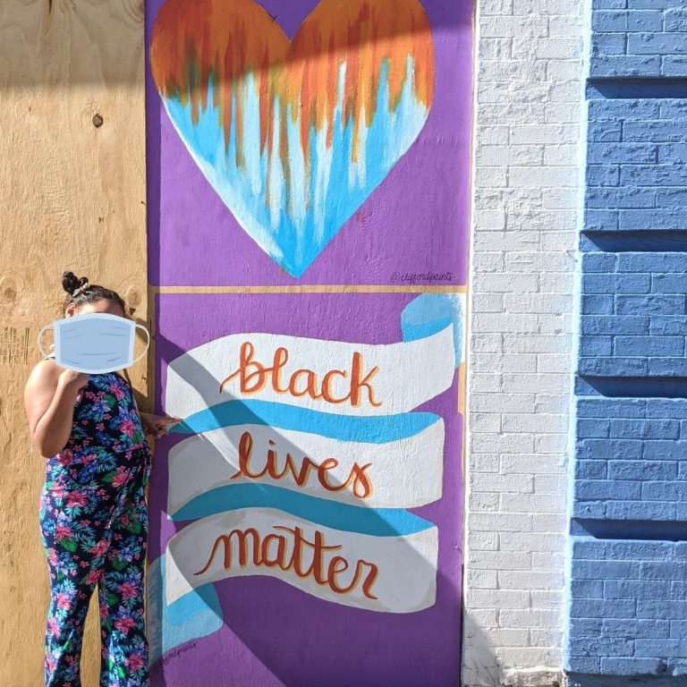 "Person standing next to Sota Letters Co mural of heart and ribbon with ""black lives matter"" text"