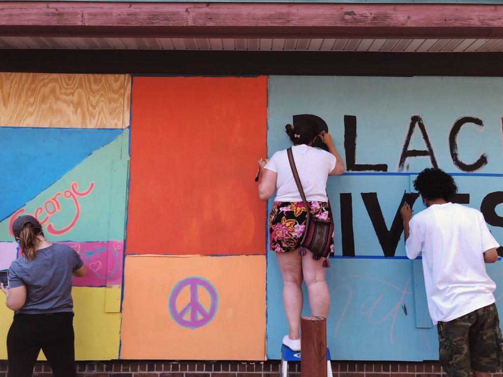 artists painting  black lives matter mural at Lotus Restaurantthree