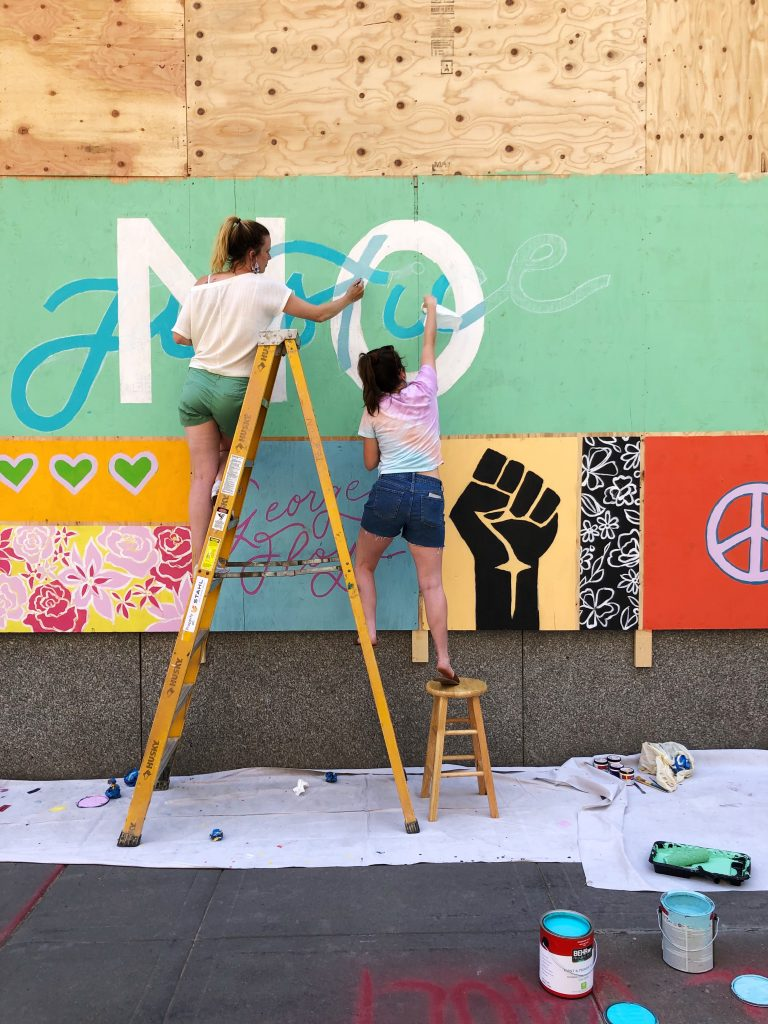 Artists on ladder and stool painting mural on boarded wall