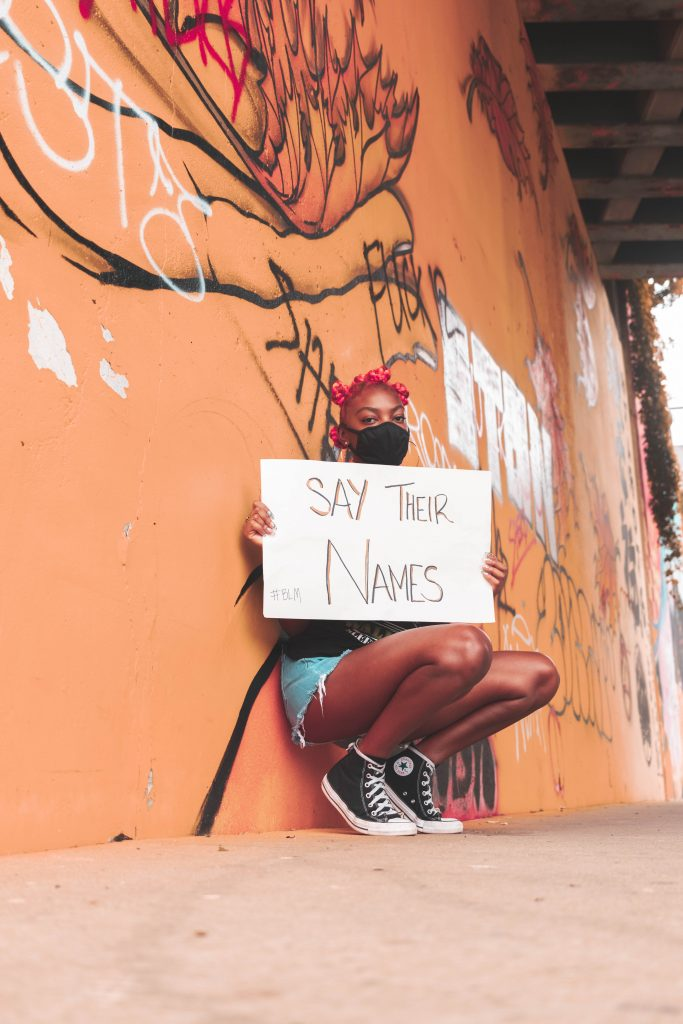 """Woman kneeling against wall holding a """"Say Their Names"""" sign"""