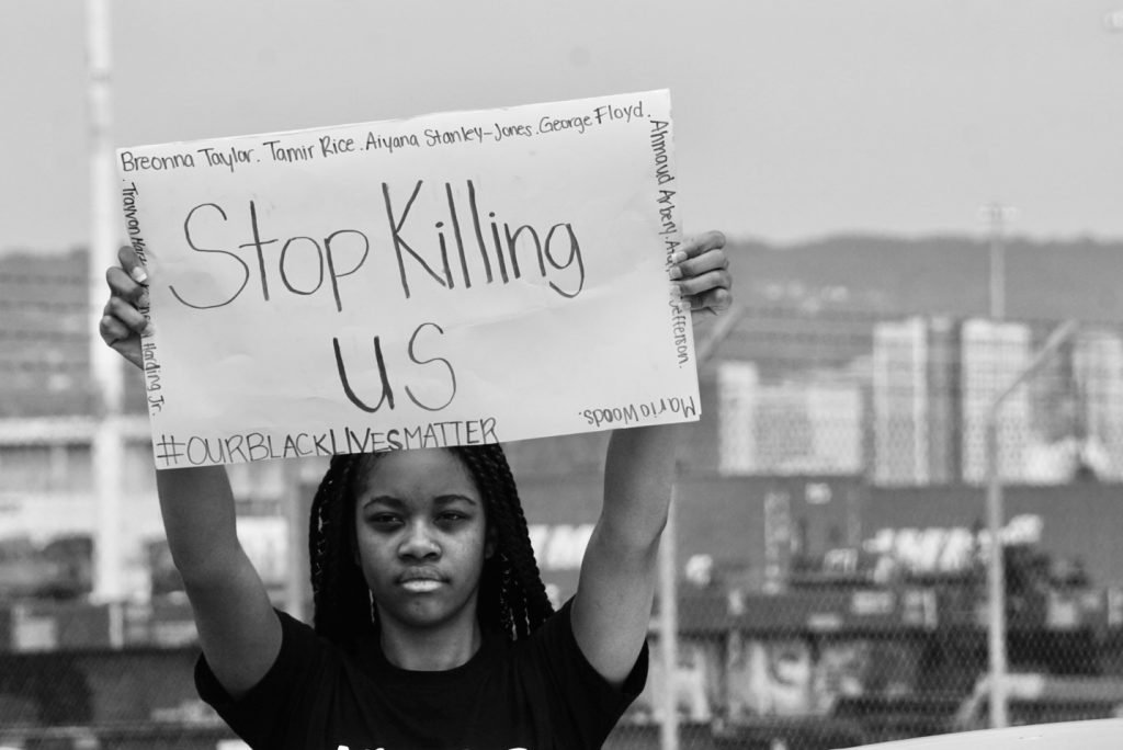 """Black woman holding """"Stop Killing Us Sign"""" in black and white"""