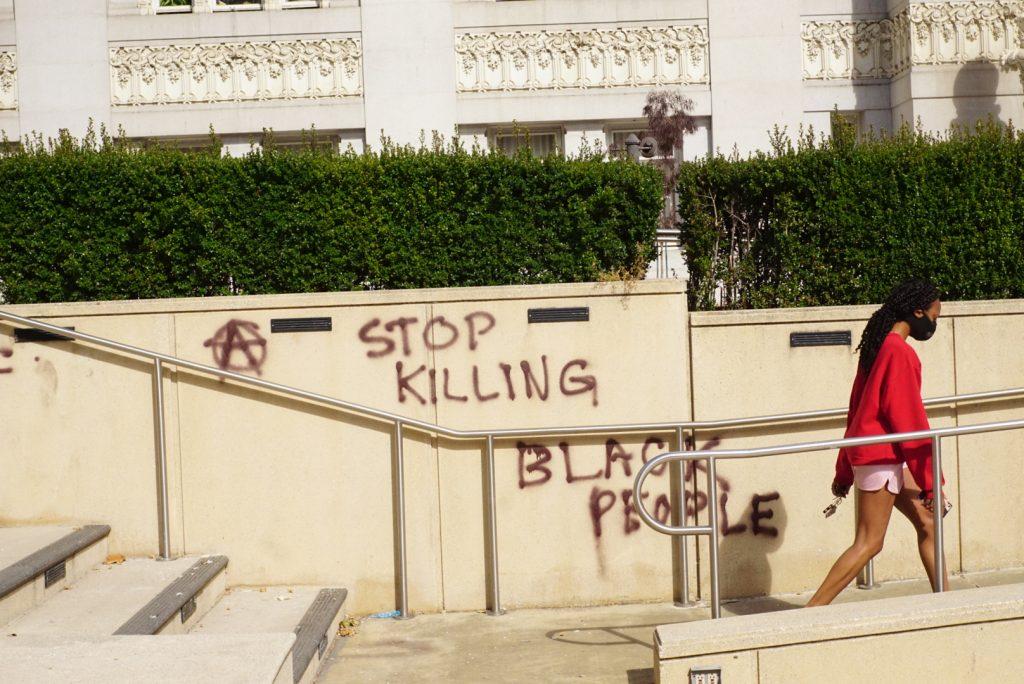 "masked black woman walking past ""Stop Killing Black People"" graffiti"