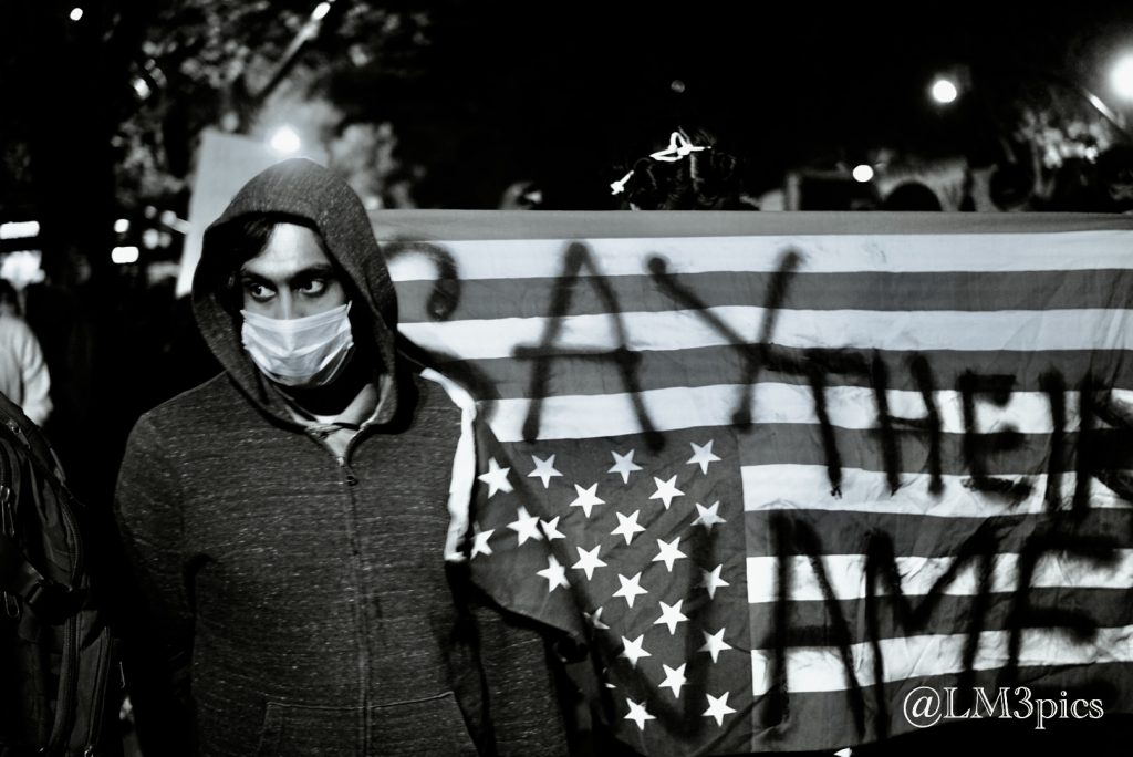 """Masked man in front of American flag spraypainted with """"Say Their Name"""" on it"""