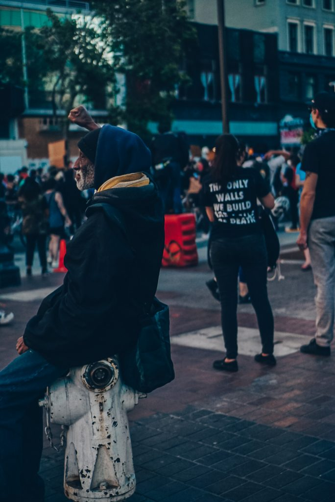 Elderly man sitting on fire hydrant holding up black power salute during protest