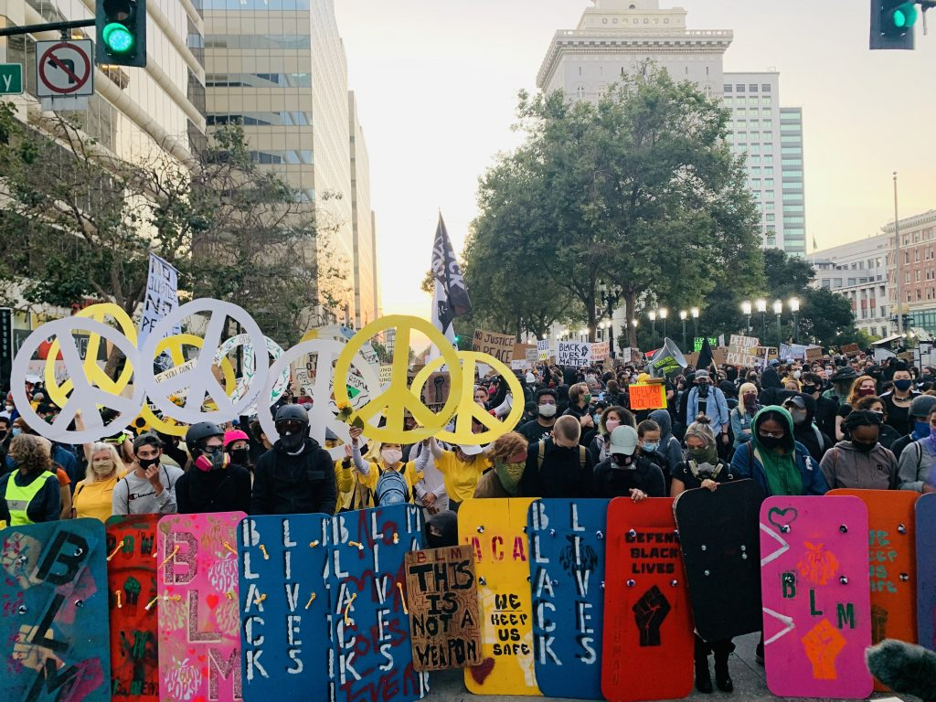 People holding colorful shields and peace signs in front of protest march