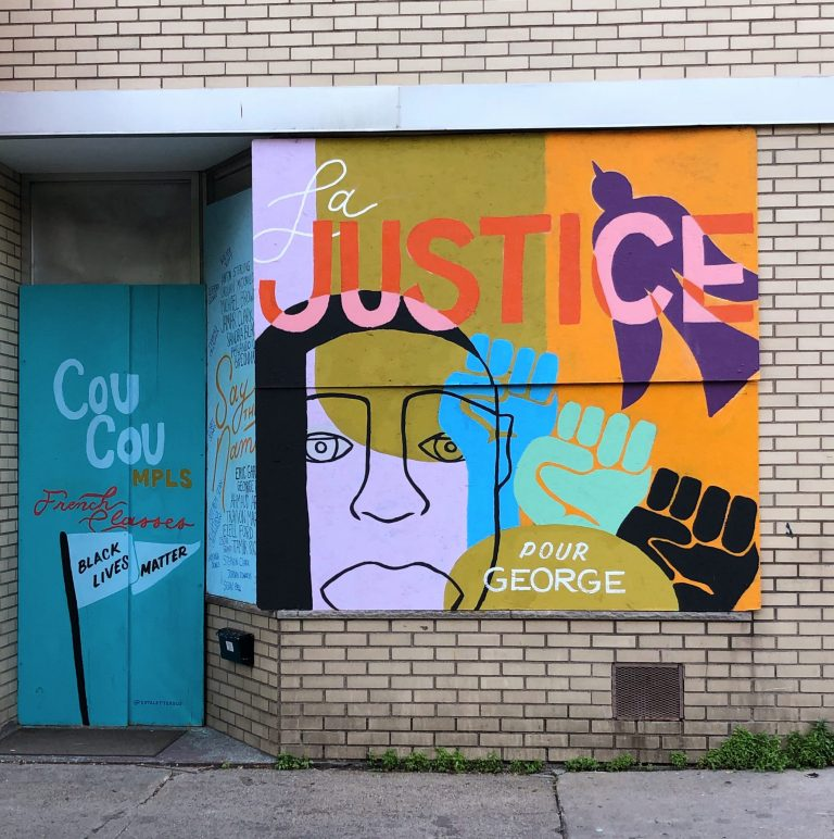 "Mural of face with raised fists and text ""La Justice pour George""."