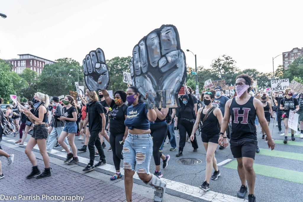 Protestors marching with two large power fist signs