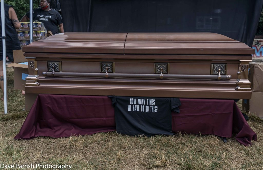 """Closed casket atop a shirt with text """"How many times we have to do this?"""""""