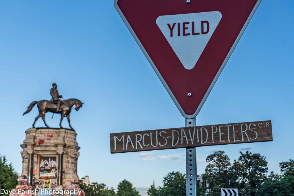 Homemade street sign names street Marcus-David Peters Cir, under yield sign with Lee statue  in background