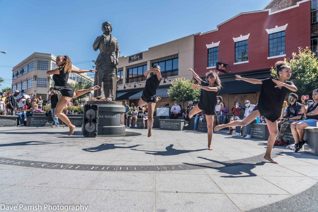 Four young girls perform dance in front of Maggie L. Walker statue in Richmond, Va.