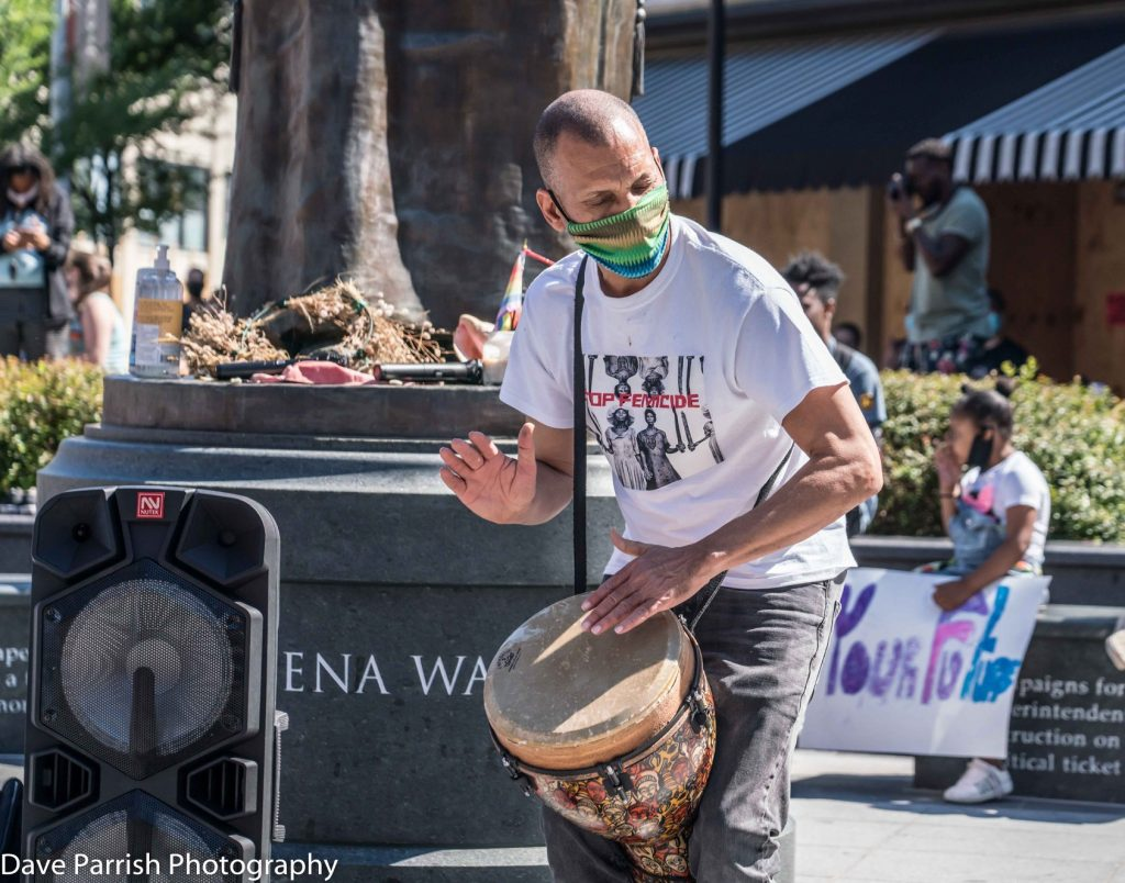 Ram Bhagat performs on drums at event near Maggie L. Walker Statue