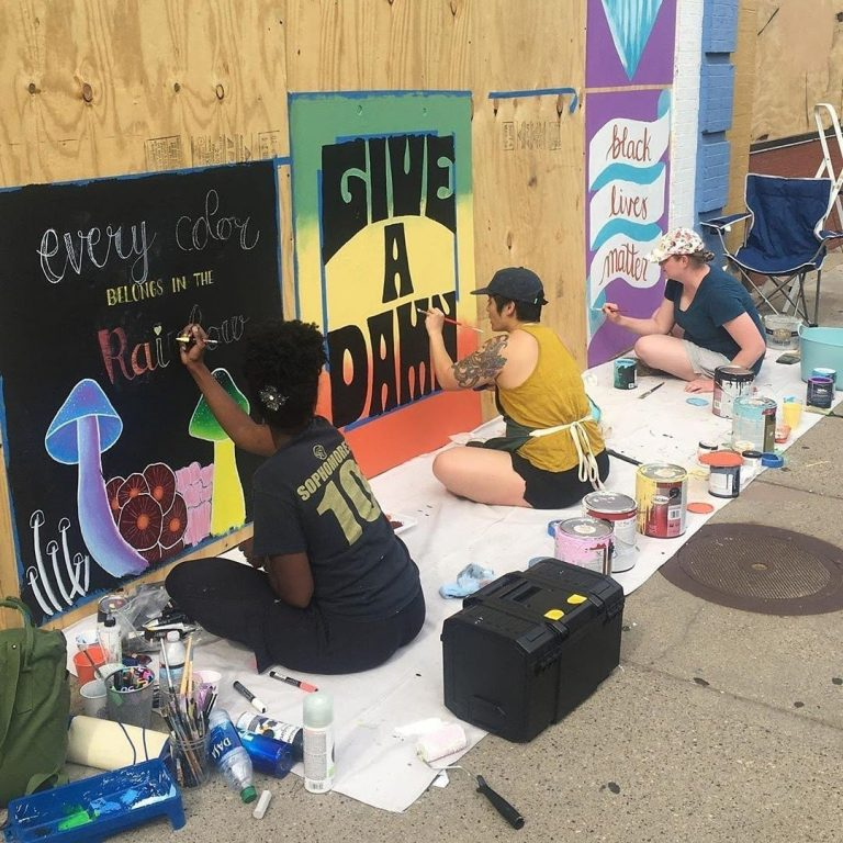 Three Sota Letters Co. artists painting a mural on boards at Jutt Salon Spa