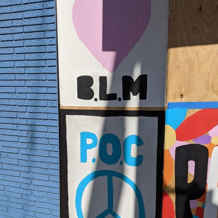 "Detail Sota Letters Co. mural with heart over ""BLM"" and ""P.O.C."" over a peace sign"