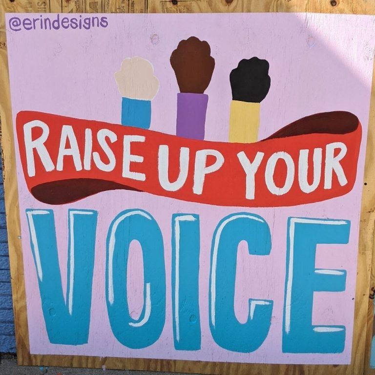 "Sota Letters Co. mural of raised fists and text ""Raise Up Your Voice"" signed by @erindesigns"