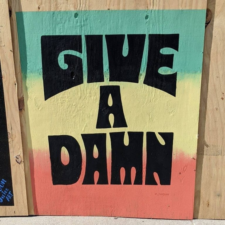 "Mural with black text ""Give A Damn"""