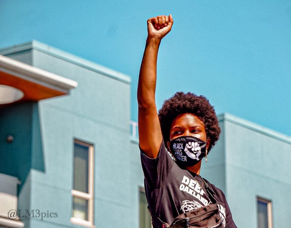 masked Black woman with afro holding up Black power salute in front of blue buildings