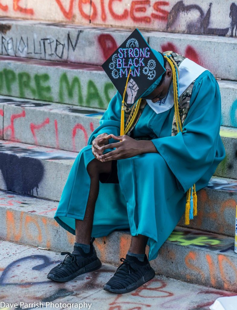 """Young black man  in graduation gown sitting on steps of General Lee monument wearing cap with """"Strong Black Man"""" on top"""
