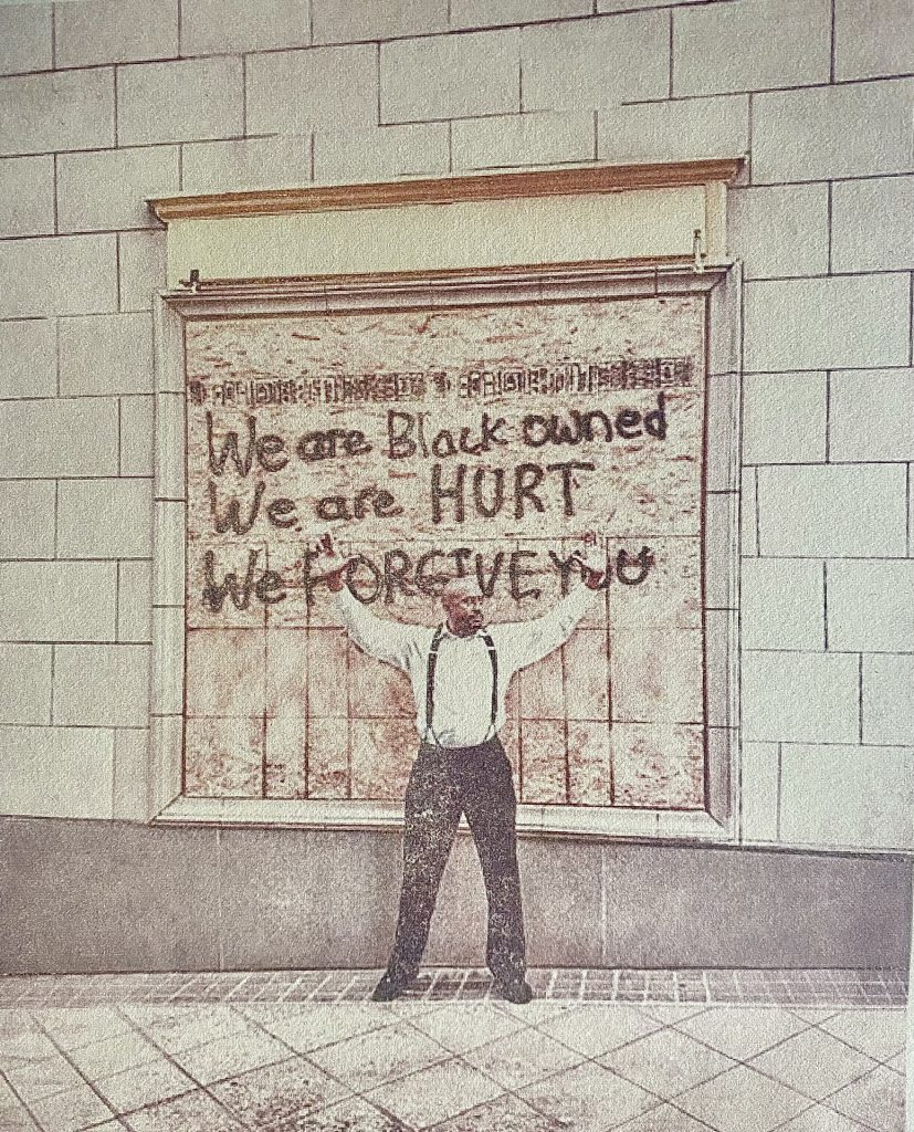 Mono-Print of image showing man with hands up in front of sign saying we are black owned we are hurt with we forgive you crossed out