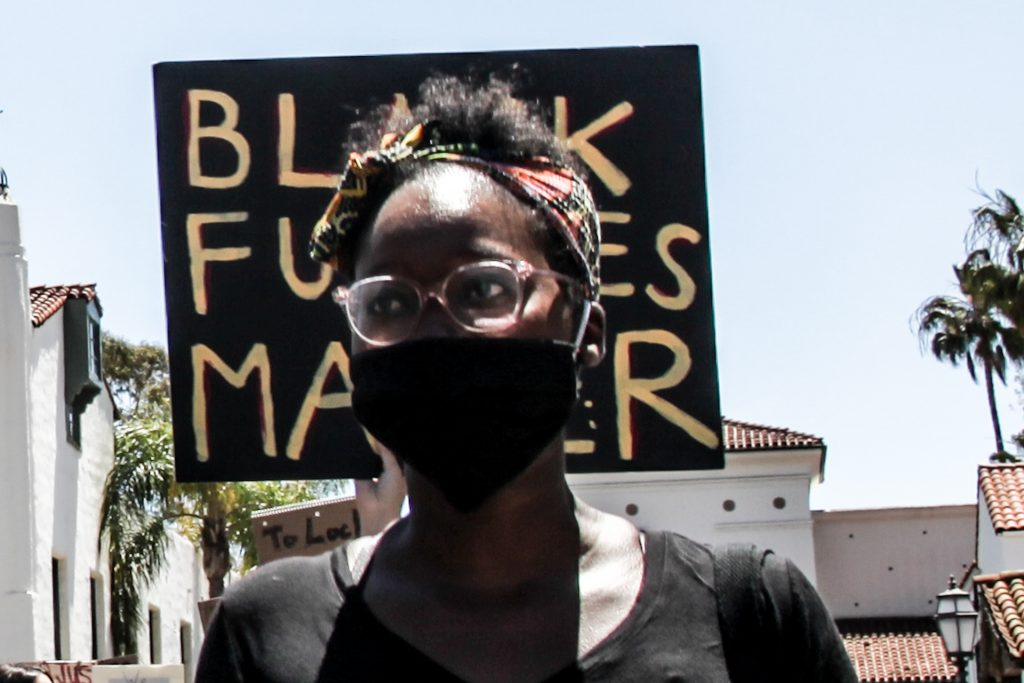 """Black Woman in mask at protest in front of """"Black Futures Matter"""" held sign"""