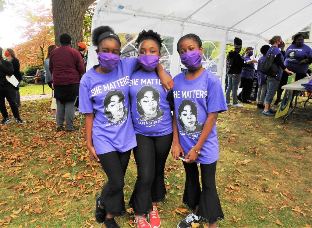 three girls posing in She Matters t-shirts with photos of Breonna Taylor on them