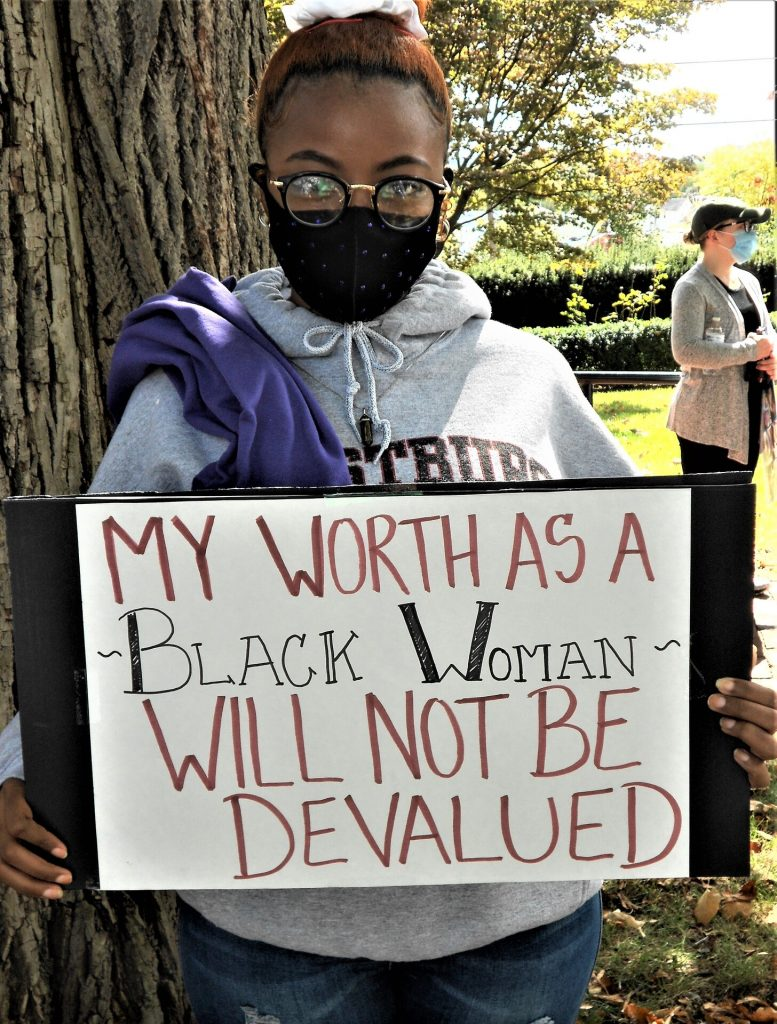 """Masked young lady holding up sign """"My worth as a Black woman will not be devalued."""""""