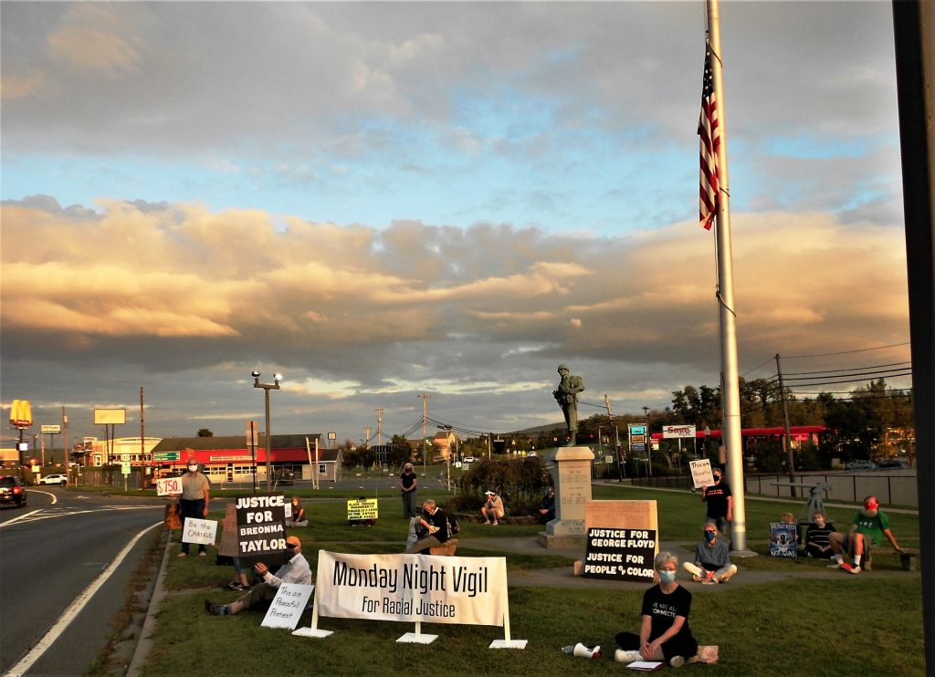 Protesters seated on grass for vigil for racial justice