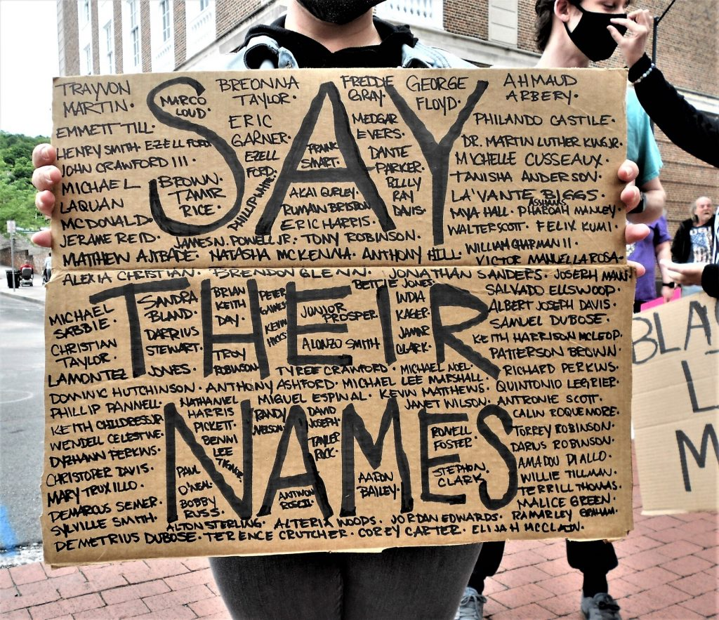 """Person holding card board sign that says """"Say Their Names"""" with a bunch of names around it,"""
