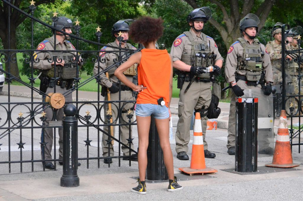 Black Woman protestor looking at a line of officers blocking a gate entrance