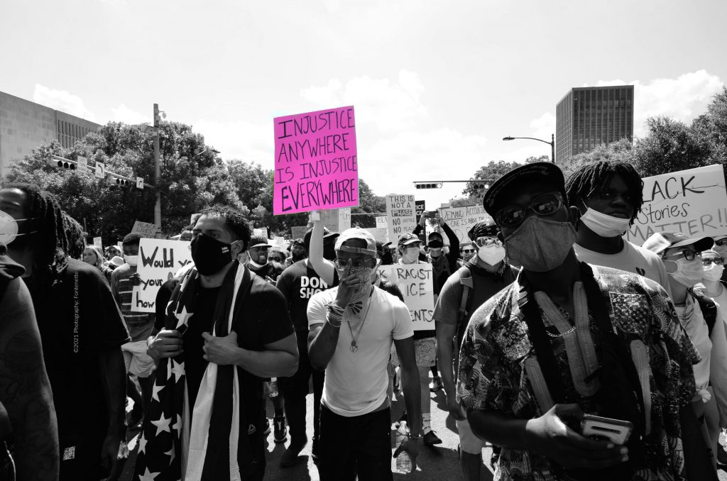 Protestors marching with signs, a man has a glag wrapped around his neck