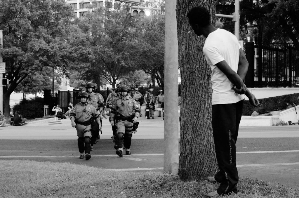 Black man watching police march towards him