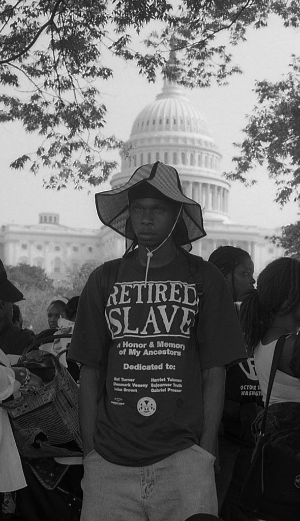 """Man wearing a shirt that says """"Retired Slave"""" standing in front of U.S. Capitol."""