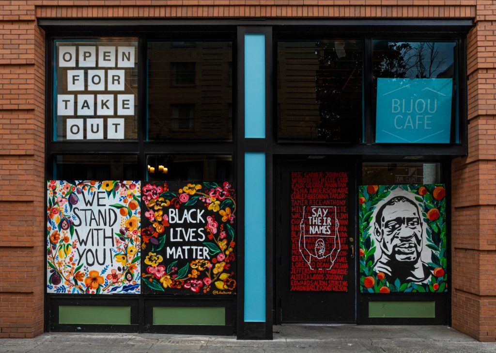 Four murals on storefront windows and doors with signage stating Open For Take Out