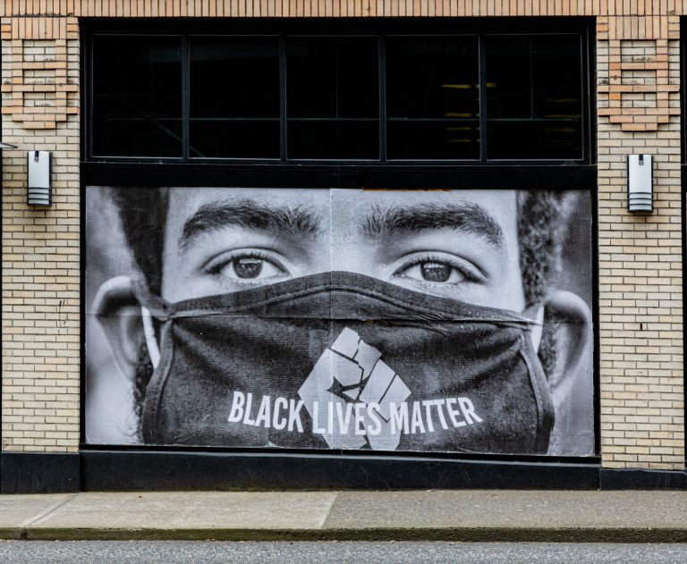 Picture of man's face wearing a Black Lives Matter Mask on a storefront window