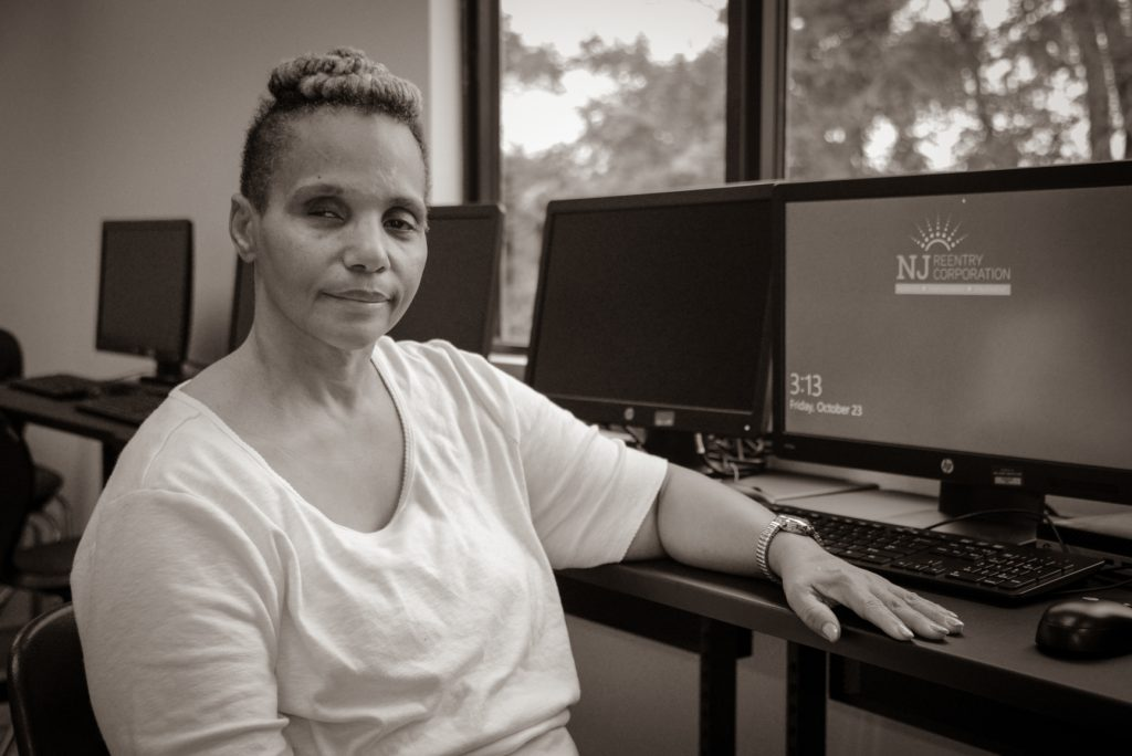 Photo of woman posing while sitting at desk with computers in background