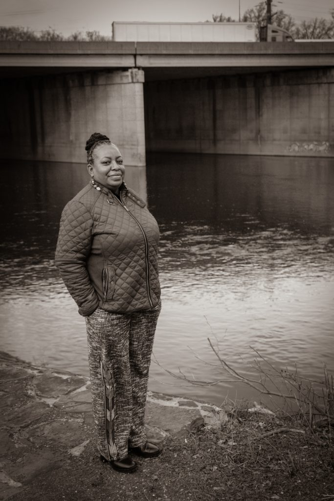 Photo of woman standing at the shore of a river