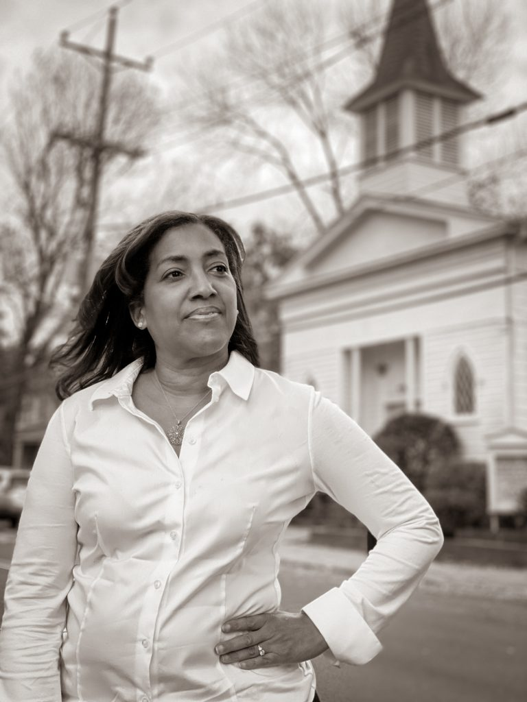 Photo of woman standing in front of a church