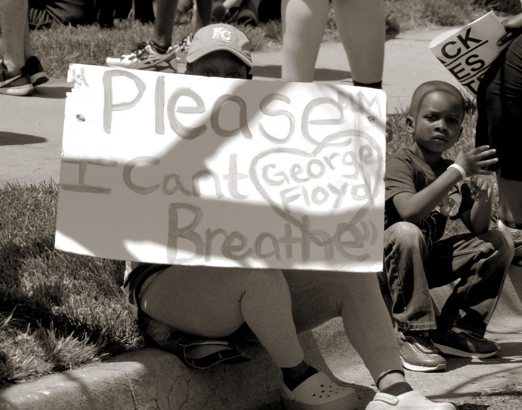 photograph of people sitting on curb with sign for George Floyd