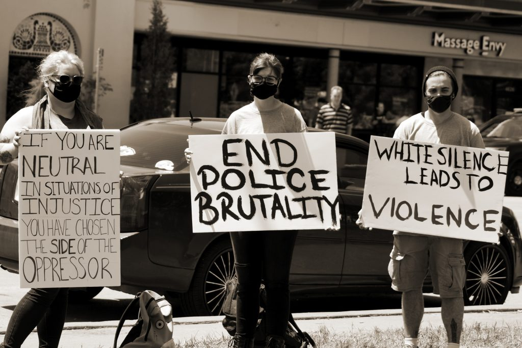 People holding signs to end police brutality and violence Black Lives Matter