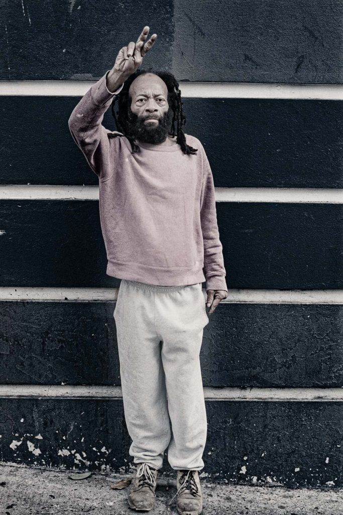 Photo of a man holding up the peace sign
