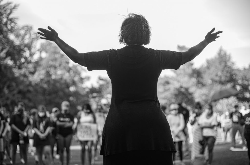 Photo of woman holding her hands to sky in front of gathered people