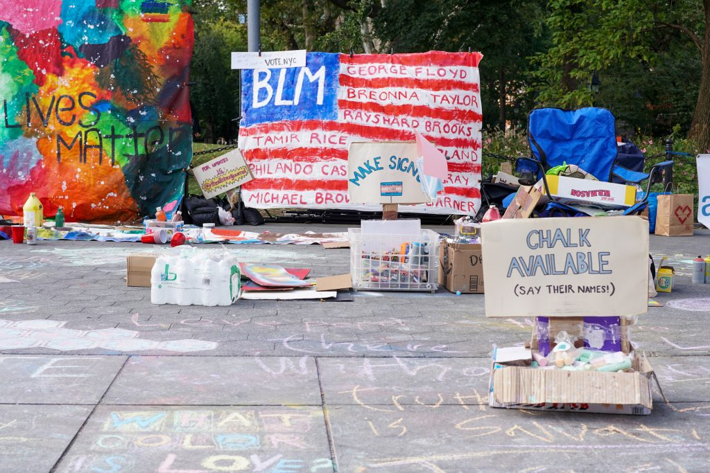 BLM protest signs on sidewalk with supplies for protestors