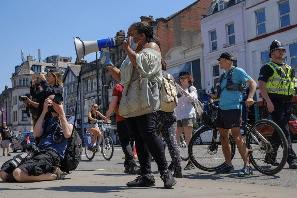 Protester with a bull horn, others on bikes and a police officer in Wales